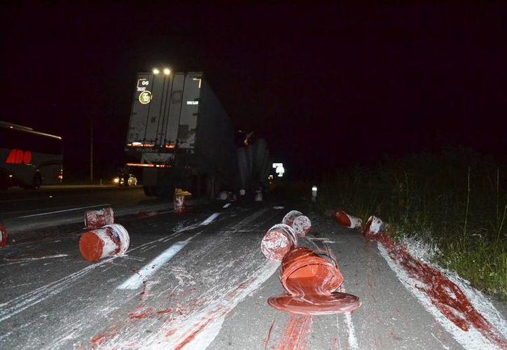 Elementos de bomberos acudieron a retirar las cubetas y la pintura que se derramó en la carretera. (Redacción/SIPSE)