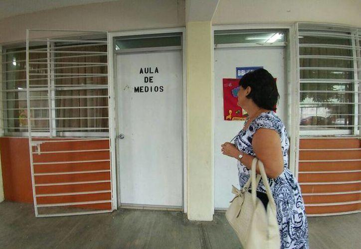 Imagen de una docente al llegar a la escuela primaria Eduardo Urzaiz para preparar el contenido del curso escolar 2016-2017. (José Acosta/Milenio Novedades)