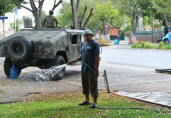 En medio de las fuertes medidas de seguridad con motivo de la Cumbres del Caribe en Mérida, un trabajador aminora a manguerazos el calor en Paseo de Montejo. (Luis Pérez/SIPSE)