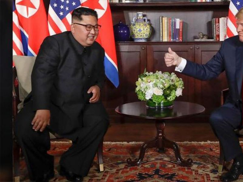 U.S. President Donald Trump holds up the document that he and North Korea leader Kim Jong Un just signed at the Capella resort on Sentosa Island.