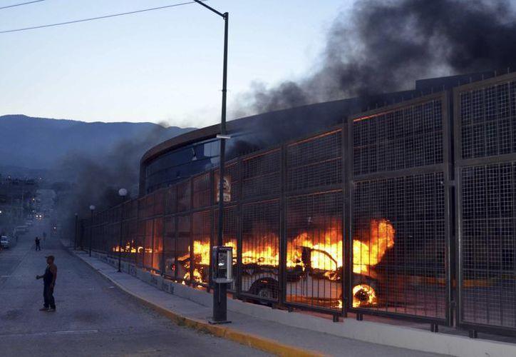 Quema de vehículos a las afueras del Palacio de Gobierno de Guerrero, a más de un mes y medio de la desaparición de 43 normalistas en Iguala, caso que aún no ha sido resuelto. (Foto: AP)