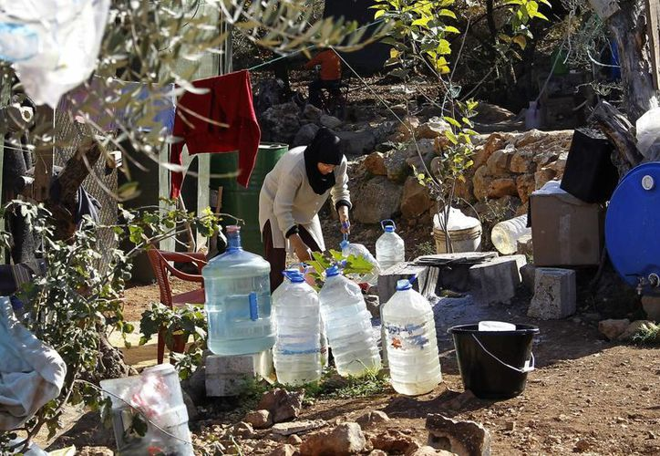 Una mujer refugiada siria llena varios bidones de agua en el campo de refugiados sirios en la localidad de Ketermaya, cerca de Sidón al sur del Líbano. (EFE)