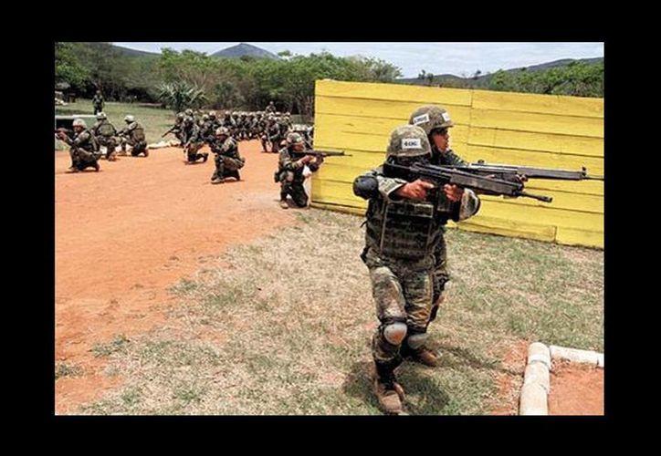 Soldados resguardan un área, mientras otros avanzan agazapados en busca de agresores. (Milenio Novedades)