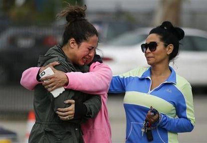 El tiroteo en San Bernardino, California es el centro de una investigación por terrorismo del FBI. En la imagen, deudos de las víctimas del ataque, a un costado de un altar improvisado (AP)