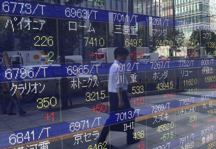 Los precios mundiales de las acciones cayeron el 12 de agosto después que China dejó caer el valor su divisa. Un peatón pasa frente a un cartel de cotizaciones en Tokio. (Agencias)