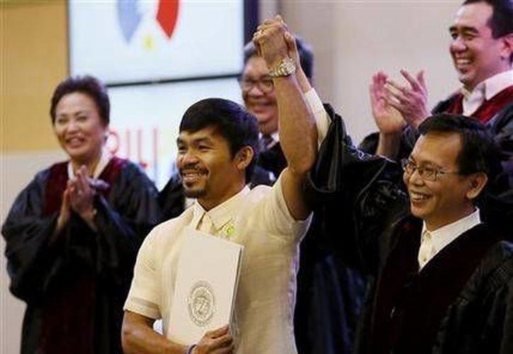 Un miembro del tribunal electoral filipino levanta el brazo de Manny Pacquiao tras confirmar que el boxeador ganó una banca en el Senado (AP Photo/Bullit Márquez).