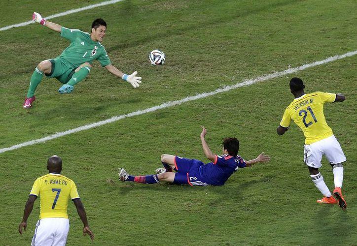 El colombiano Jackson Martínez anota pese al esfuerzo de Atsuto Uchida y el portero japonés Eiji Kawashima. (Foto: AP)