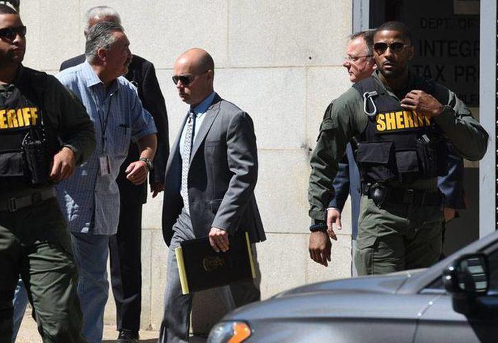 Policías escoltan al agente Brian Rice (centro) a su salida de la Corte, luego de ser declarado inocente de la muerte de Freddy Gray, el lunes 18 de julio de 2016 in Baltimore, Maryland, EU. (Foto: Jerry Jackson/Baltimore Sun vía AP)