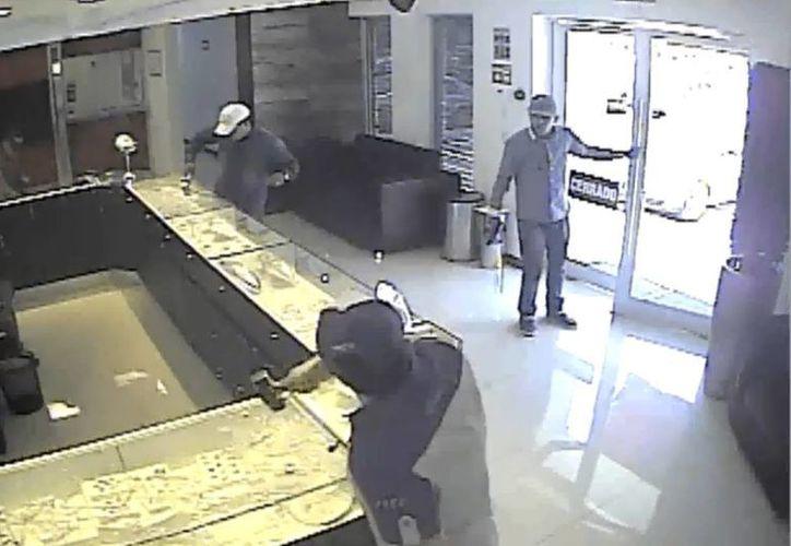Dos delincuentes entraron al local armados, mientras que otros tres se hicieron pasar por clientes y rompieron las vitrinas. (Captura de pantalla del video)