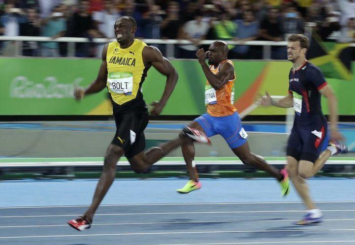 Usain Bolt (i) mostró cansancio, sufrimiento, pero al final celebró su triunfo en los 200 metros planos de Río 2016 (AP)