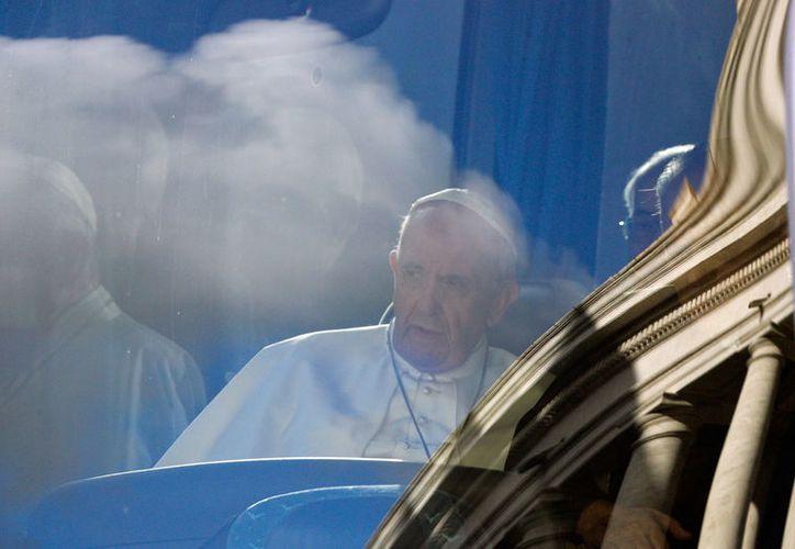 El Papa visto a través de la ventanilla de un autobús al pasar por El Vaticano. Francisco dejó su retiro espiritual del fin de semana en la villa de Ariccia, para el Angelus de este domingo, en que el exhortó a leer más la Biblia. (AP/Gregorio Borgia)