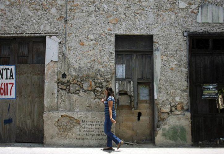 Imagen de una joven caminando por un edificio de la entidad, el cual presenta afectos del cambio climático. (Milenio Novedades)