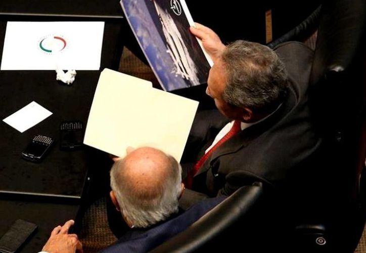 Los senadores priistas Carlos Romero Deschamps y Gerardo Sánchez mientras consultan un catálogo de yates en el Senado. (Imagen de Agencia Reforma publicada por proceso.com.mx)