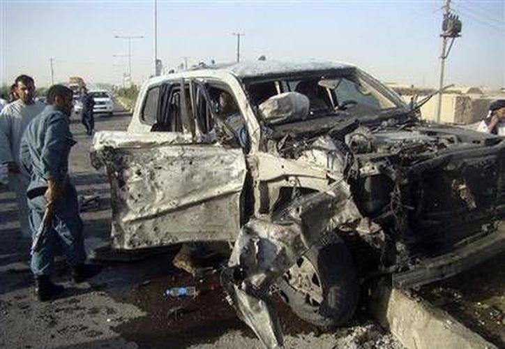 Policías afganos investigan un automóvil semidestruido después de un ataque suicida en la provincia de Helmand en Afganistán. (Agencias)