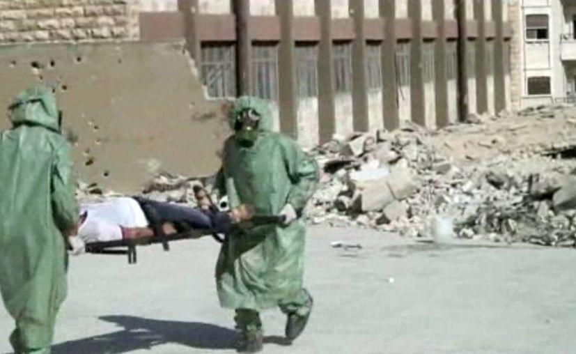 Sirios con trajes de protección y máscaras antigás realizar un ejercicio sobre cómo tratar a las víctimas de un ataque con armas químicas. (Agencias)