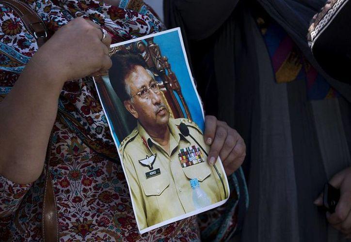 Una simpatizante de Musharraf sostiene una foto del expresidente afuera de la corte en Islamabad. (Agencias)