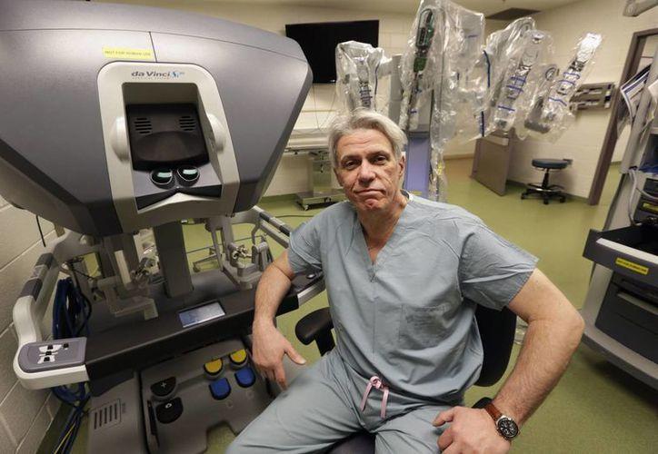 El doctor Pier Giulianotti aparece delante del polémico robot-cirujano. (Agencias)