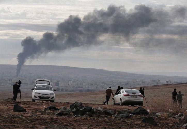Periodistas observan columnas de humo que siguen a bombardeos afuera de la ciudad turca de Suruc, que limita con Siria, este domingo 19 de octubre de 2014. (Foto: AP)