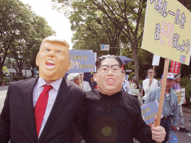 Protesters wearing masks of U.S. President Donald Trump, left, and North Korean leader Kim Jong Un, march in Tokyo. (AP)