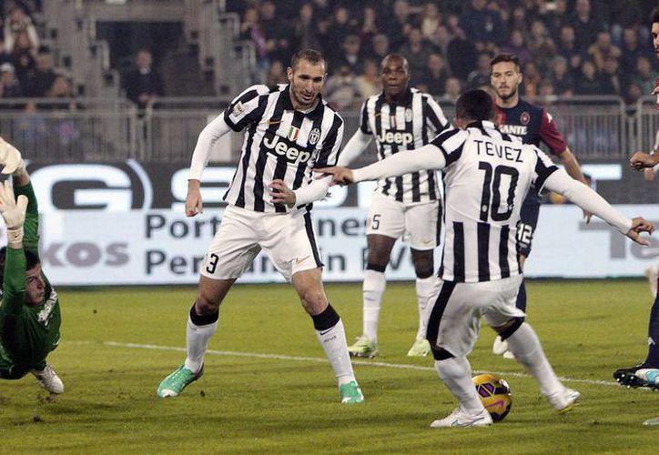 Carlos Tévez (d) se dispone a meter un gol en el partido que su equipo Juventus ganó a Cagliari dentro de la Liga de Italia. (Foto: AP)