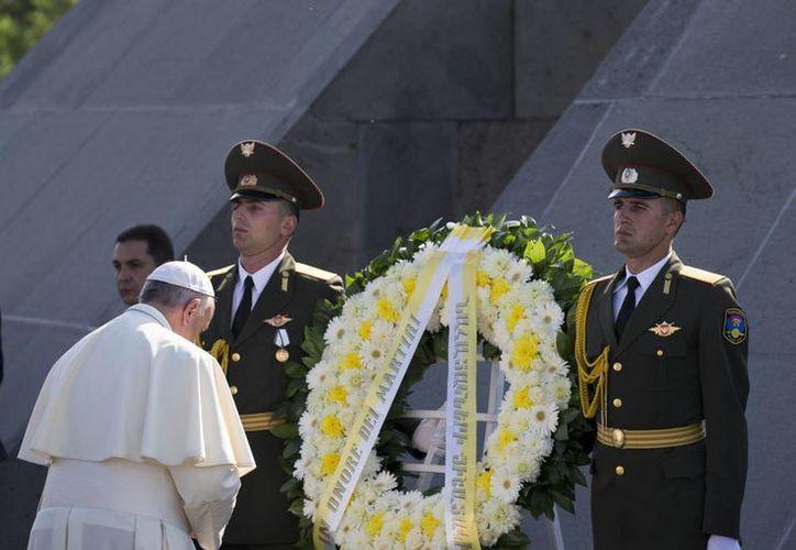 El Papa Francisco colocó una corona en el monumento que recuerda la masacre y rezó en silencio de pie, con la cabeza gacha. (Agencias)