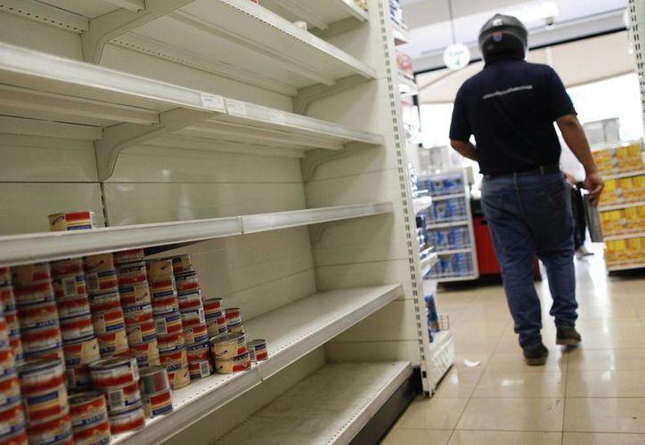 La economía venezolana cerró el año pasado con una inflación superior al 50 % y un crecimiento de apenas 1.6 %, en medio de una crónica escasez de bienes en los supermercados y una amplia brecha entre el tipo de cambio oficial y el ilegal paralelo. (EFE)