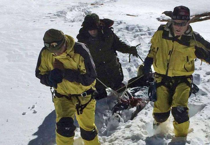 Rescatistas transportan el cuerpo de una víctima de una avalancha en la zona del paso Thorong La, Nepal. (Agencias)