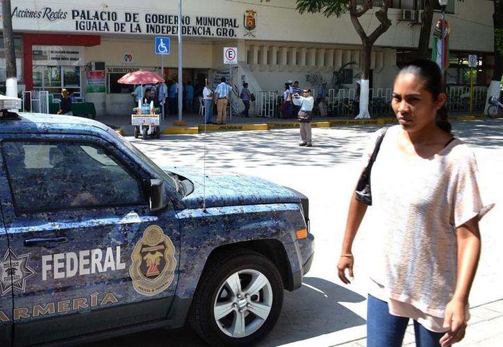 Una ciudadana pasa frente al Palacio Municipal de Igual, sede de la Administración Municipal donde todavía despachan 30 parientes del prófugo alcalde con licencia, José Luis Abarca. La imagen es de contexto. (NTX)