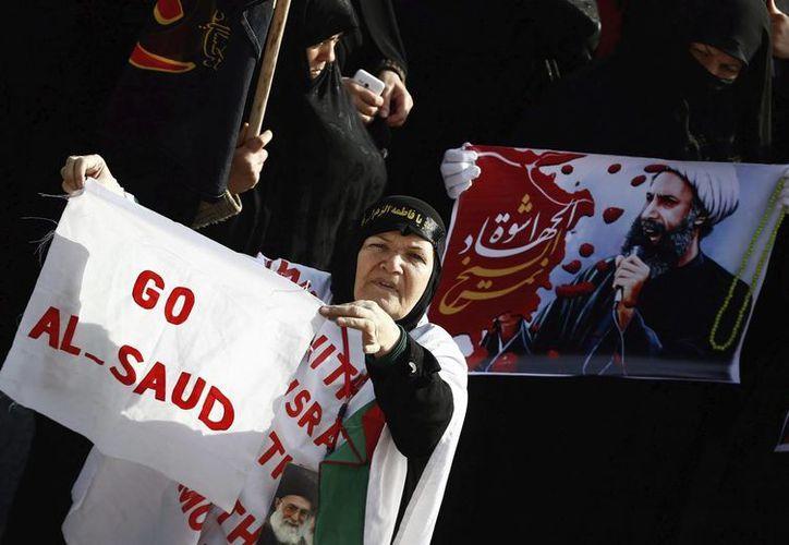Las relaciones entre Irán y Arabia Saudita atraviesan una crisis después de que las autoridades de Riad ejecutaran al clérigo y dirigente chií, Nimr Baqir al Nimr. Manifestantes iraníes muestran carteles con el retrato del clérigo y dirigente chií, Nimr Baqir al Nimr, durante una protesta convocada en Teherán. (Agencias)