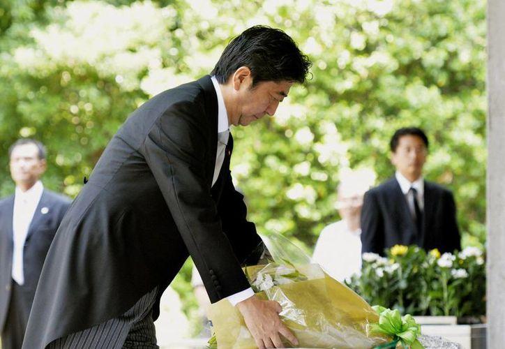 Shinzo Abe coloca un arreglo floral en el cementerio  Chidorigafuchi, donde están los restos de víctimas no identificadas de la Segunda Guerra Mundial. (Agencias)