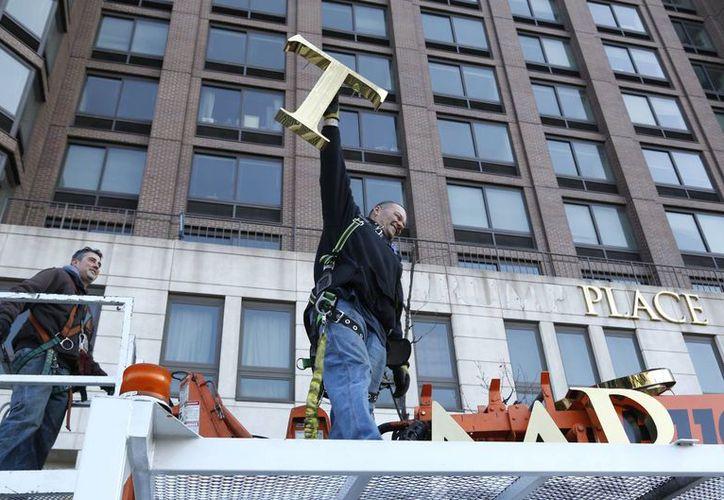 Un trabajador alza la letra T al retirar las letras de un edificio antes conocido como Trump Place en Nueva York. (AP/Seth Wenig)