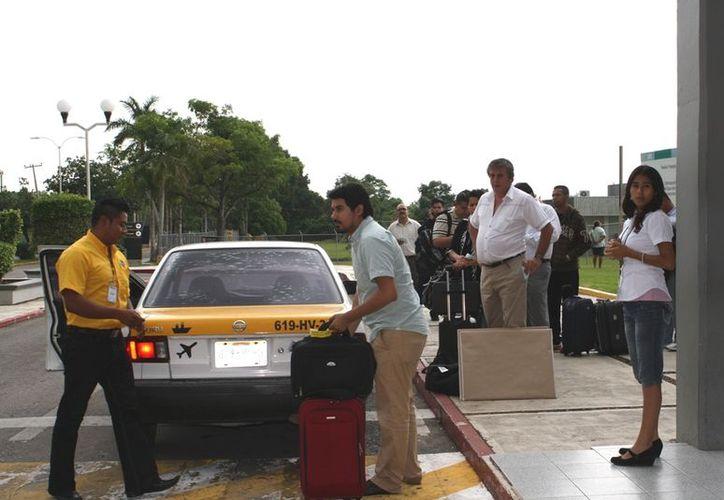 Los 145 pasajeros, en promedio, que llegan de dos vuelos procedentes de la Ciudad de México esperarán menos para abordar un taxi de sitio federal la semana próxima. (Enrique Mena/SIPSE)