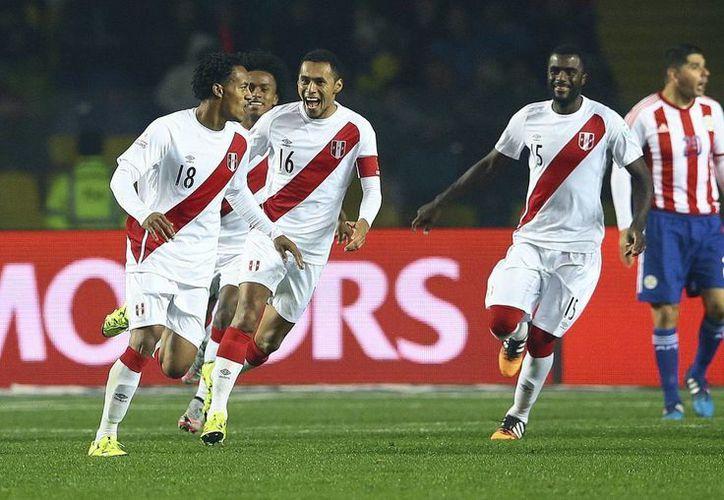El delantero peruano André Carrillo (i) celebra el primer gol de su equipo marcado ante Paraguay durante el partido por el tercer puesto de la Copa América de Chile 2015, en el Estadio Municipal Alcaldesa Ester Roa Rebolledo de Concepción, Chile. (EFE)