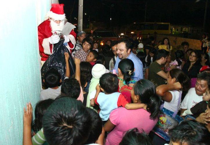 Decenas de pequeños esperan ansiosos un regalo de Santa Claus, ayudado por 'Panchito' Torres. (Cortesía)