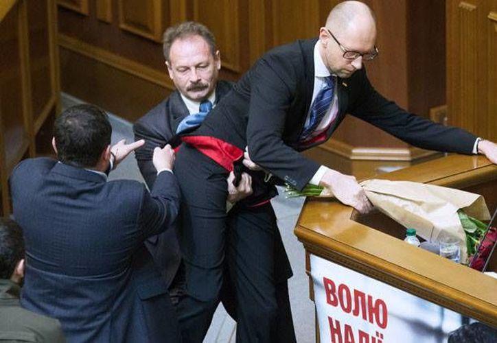Momento en que Oleg Barna trata de quitar del estrado al primer ministro de Ucrania, Arseni Yatseniuk. (sputnikimages.com)