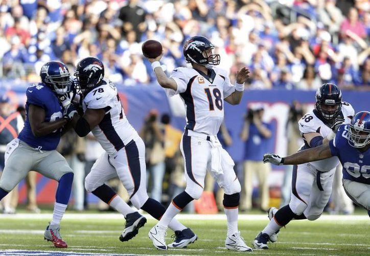 Peyton Manning (c) tiene nueve pases de anotación, la mejor marca en la historia de la NFL para los dos primeros partidos de una nueva temporada. (EFE)