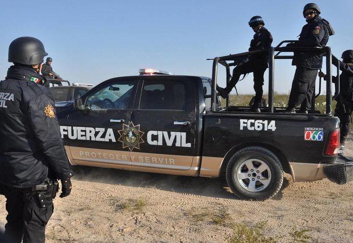 Policías del estado de Nuevo León en guardia junto a un camino de terracería hacia una finca cerca del pueblo de Mina. (Agencias)
