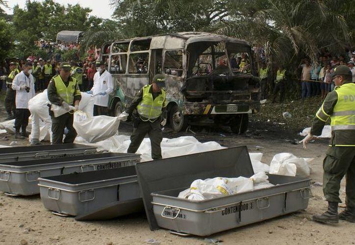 Policías trasladan los cuerpos de los niños que fallecieron el domingo en un accidente de autobús. (Agencias)