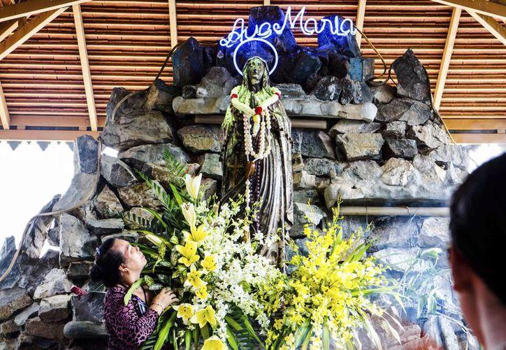Una mujer observa una de las dos estatuas de la Virgen María durante el tercer aniversario del descubrimiento de la otra estatua en el río Mekong, en el pueblo de mayoría vietnamita Arey Ksat, en la provincia de Kandal al sur de Camboya. (EFE)