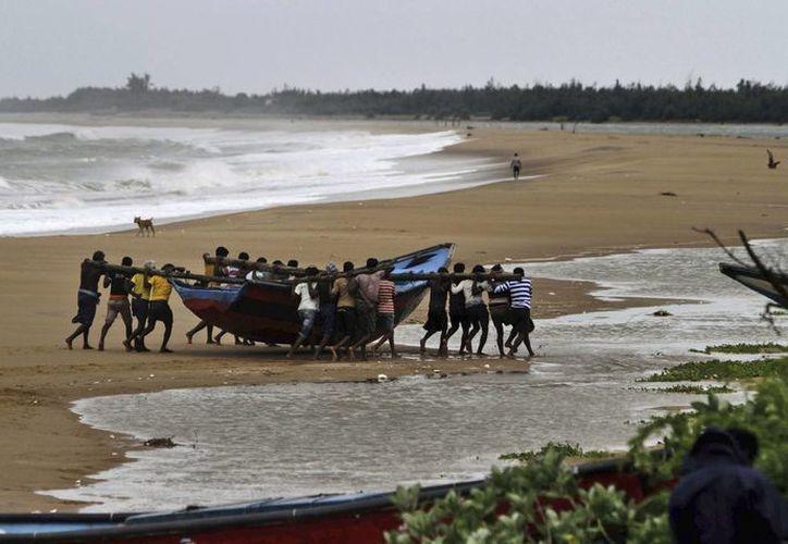 Pescadores en India mueven una barca ante la cercanía del ciclón Hudhud. (Foto: Ap)