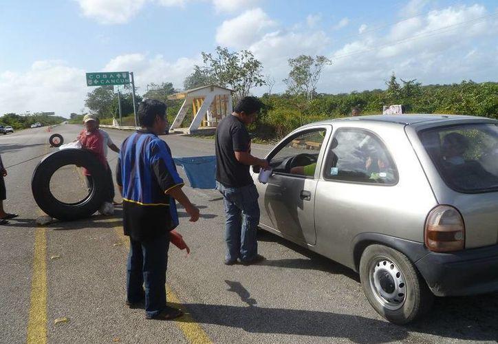 Los ejidatarios siguen cobrando una cuota a los automovilistas. (Raúl Balam/SIPSE)