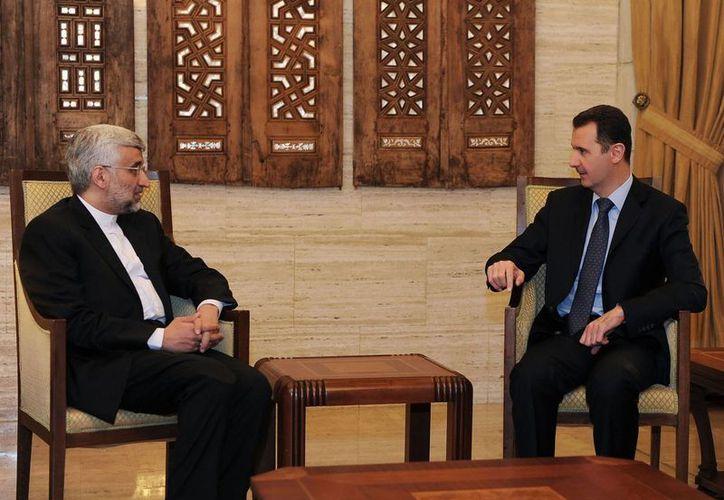 El presidente sirio, Bashar Assad (der), se reúne con el jefe negociador nuclear iraní, Saeed Jalili. (Agencias)