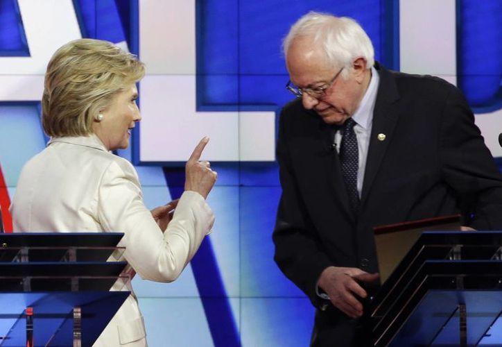 La precanditada demócrata Hillary Clinton y su contrincante Bernie Sanders durante un descanso del debate que sostuvieron la noche del jueves en el Navy Yard de Brooklyn. (Agencias)