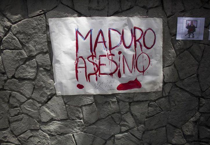 Imagen de un letrero colocado por manifestantes en el que llaman asesino al presidente Maduro, fuera de la misión diplomática del Vaticano en Caracas, Venezuela. (Agencias)