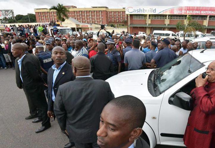 Imagen facilitada por la oficina de prensa del Gobierno sudafricano, en la que aparece el presidente Jacob Zuma (d) reodeado de una multitud, en su visita a uno de las localidades en la que se han registrado ataques xenófobos. (EFE)