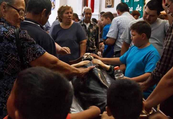 Varios devotos tocan la imagen de San Francisco Javier en el interior de la iglesia de Magdalena de Kino, Sonora. (Agencias)