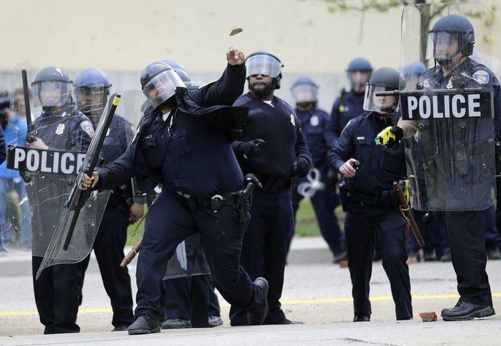 Policías se enfrentan a manifestantes en Baltimore en el marco del funeral de Freddy Gray, muerto horas después de ser arrestado, lo cual obligó a la cancelación de un juego de Grandes Ligas entre Orioles y Medias Blancas. (Foto: AP)
