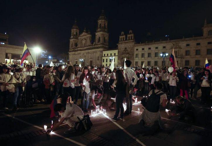 En la capital colombiana, Santa Fe de Bogotá, miles de personas colmaron la plaza principal para exigir 'Acuerdo de paz ya'. (AP/Fernando Vergara)