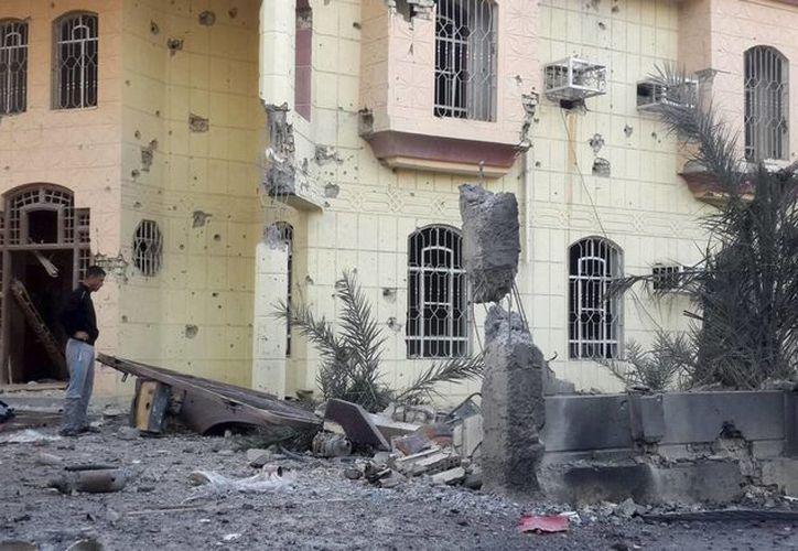 Varios ciudadanos observan los daños de una casa tras un ataque aéreo del ejército iraquí en Faluya, el pasado mes de marzo. (EFE/Archivo)