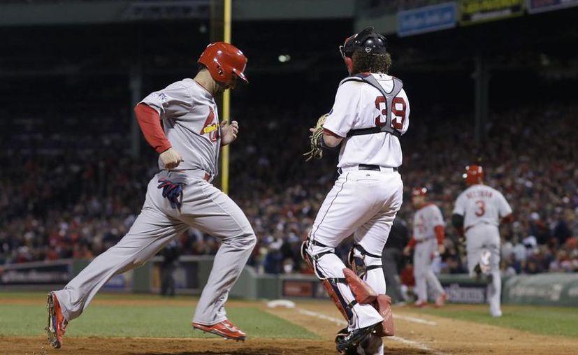 El cardenal Daniel Descalso anota frente al catcher de Boston, Jarrod Saltalamacchia (39),  en la séptima entrada. (Agencias)